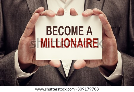 Become a Millionaire. Man holding a card with a message text written on it - stock photo
