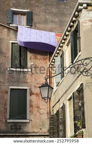 Bed cover drying at a window, Venice, Italy - stock photo