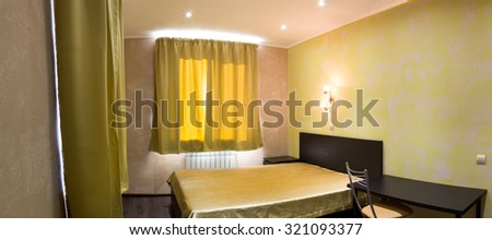 bed in the bedroom in shades of yellow