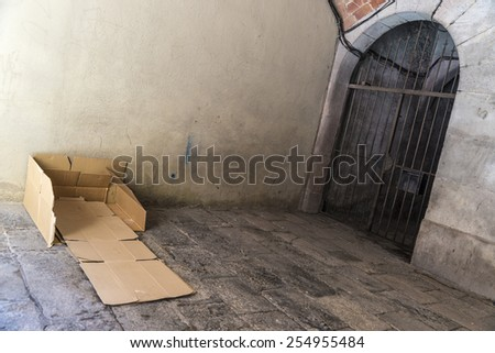 Bed made of cartons of a homeless man on a street covered with old stone floor of the old town of Barcelona. - stock photo