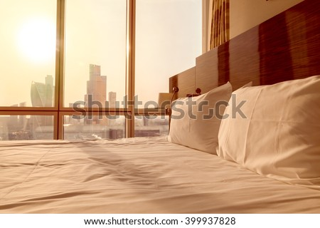 Bed maid-up with clean white pillows and bed sheets in empty room. Close-up. Lens flair in sunlight. Sunrise city view on the background - stock photo