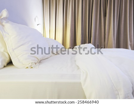 Bed sheet and pillow unmade in bedroom - stock photo