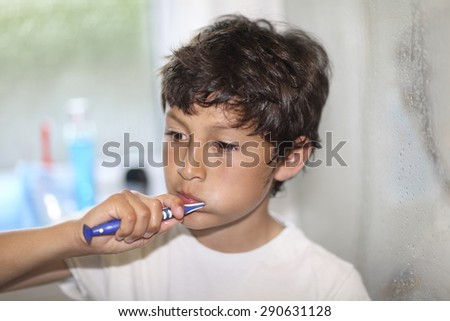 Bed time - boy brushes his teeth - very shallow depth of field - stock photo