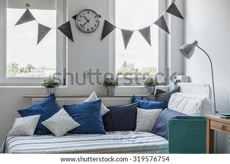 Bed under the window in boy's room - stock photo