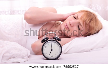 Bed woman covering ears  because of noise