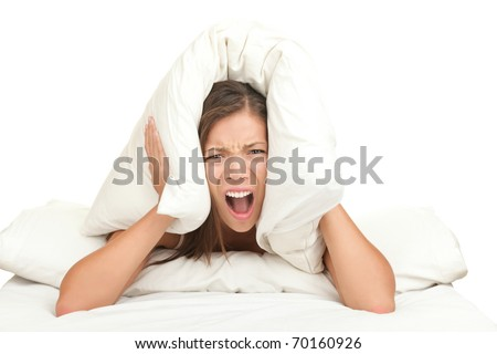 Bed woman covering ears with pillow because of noise. Funny image isolated on white background.