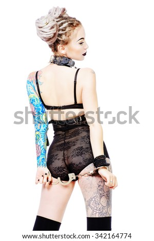 Beddable young woman alluring in sexy lingerie and handcuffs. BDSM. Isolated over white. - stock photo