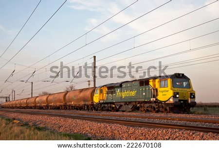 BEDFORD, UK - MARCH 19:A Freightliner locomotive taking cement to the south coast passes Bedford embankment on March 19, 2014 in Bedford. FLT founded in 1995 has an operating revenue of approx £360Mn  - stock photo