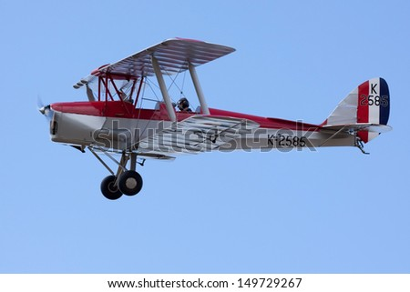 BEDFORDSHIRE, UK - AUGUST 11: A De Havilland DH.82A Tiger Moth, G-ANKT / K2585 in flight at the Air show on August 11, 2013 at Shuttleworth, Old Warden Park, Bedfordshire, UK.