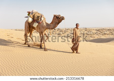Bedouin and camels in sand dunes in desert under clean sky - stock photo