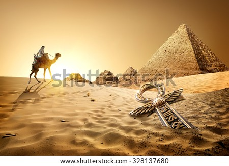 Bedouin on camel near pyramids and ankh in desert - stock photo