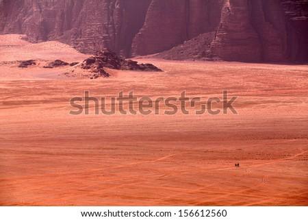 Bedouins riding on camels in the dessert of Wadi Rum in Jordan - stock photo