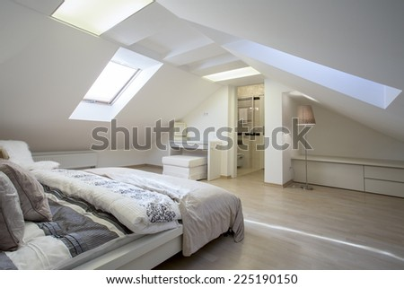 Bedroom connected with bathroom in the attic - stock photo