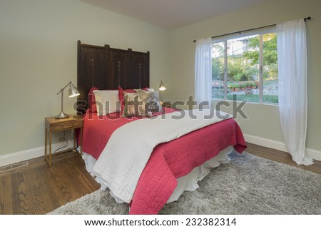 Bedroom decorated in red and white bedspread and curtains. - stock photo