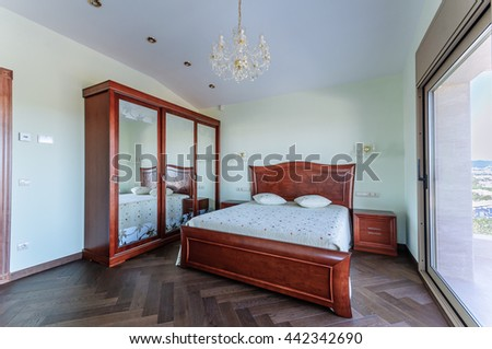 Bedroom in classic style.  Luxury mahogany furniture. Wardrobe with mirrors. - stock photo