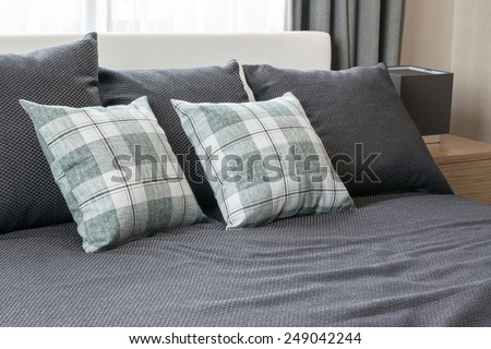 bedroom interior design with checked green pillows on grey bed and decorative table lamp. - stock photo