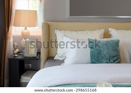 bedroom interior design with white and green pillows on white bed and decorative table lamp. - stock photo
