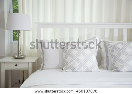 bedroom interior design with white pillows on bed and decorative table lamp. - stock photo