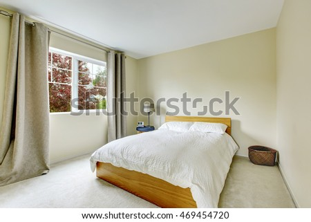 Bedroom interior in light tones with wooden bed and carpet floor. Northwest, USA