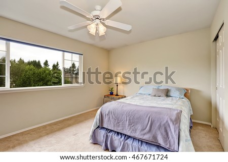 Bedroom interior in pastel blue and beige color. There is also a built-in closet, large window and carpet floor. Northwest, USA