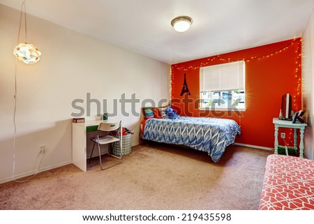 Bedroom interior with bright red wall. Furnished with a single bed, desk and table with tv - stock photo