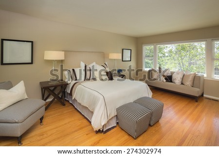 Bedroom interior with furnishing in neutral colors on an uncarpeted hardwood floor. - stock photo