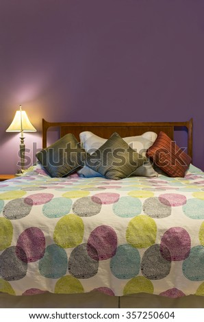 bedroom interior with lamp colorful pillows and comforter decorating queen size bed and purple wall  - stock photo