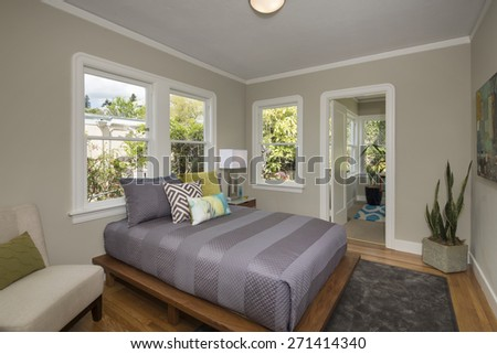 Bedroom with amazing wooden bed frame and decorated big expansive violet mattress with matching pillows in modern home.  - stock photo