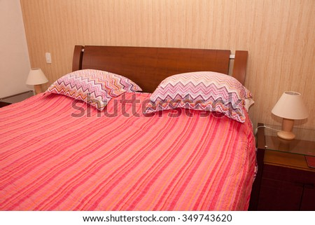 Bedroom with bed made and red cover - stock photo