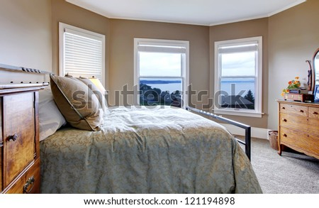 Bedroom with brown walls, simple bed and water view. - stock photo