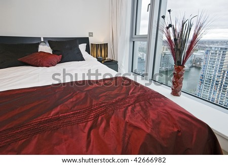 bedroom with floor to ceiling window and city views