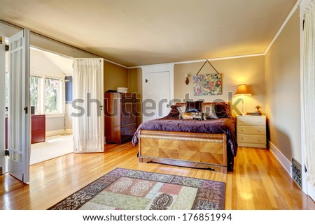 Bedroom with hardwood floor rug. Furnished with antique dresser cabinet and carved wood bed. Room has a walkout bright office room - stock photo