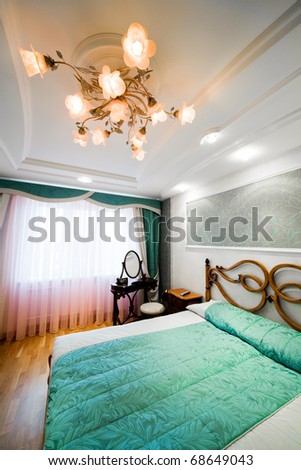 Bedroom with the chandelier in modern  apartment - stock photo