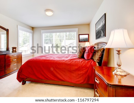 Bedroom with two windows and red bed with wood furniture with beige carpet. - stock photo