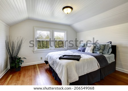 Bedroom with wood plank paneled walls and ceiling. View of black queen size bed and dry branches in the corner - stock photo