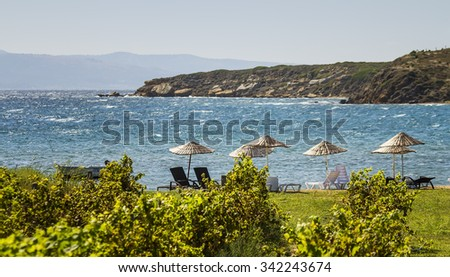 Beds and Straw Umbrellas On A Beach On A Windy Day By Grape Vines At Bozcaada, Canakkale, Turkey - stock photo