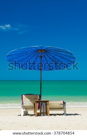 beds and umbrella on a tropical beach