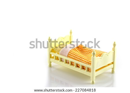 Beds yellow toy With blankets and pillows on white background - stock photo