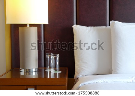 bedside table and lamp in hotel room - stock photo