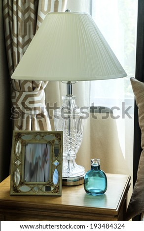 Bedside table with lamp, and picture frame - stock photo