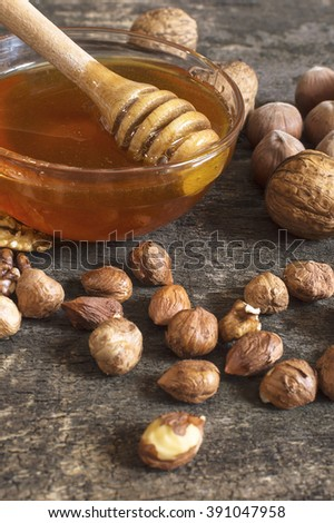 Bee honey in a glass jar, hazelnuts and walnut, on an old vintage wooden table. Healthy eating style concept. Selective focus. - stock photo
