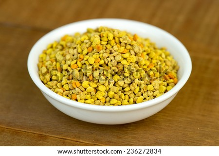 Bee pollen closeup in white bowl on wooden table - stock photo