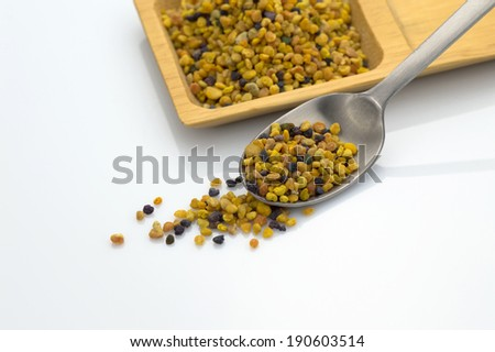 bee pollen grains with spoon on white background - stock photo