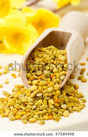 bee pollen in wooden scoop, yellow flowers as background - stock photo