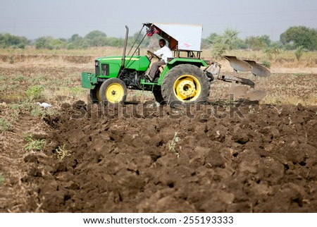BEED, MAHARASHTRA, INDIA - March 25, 2012: Farmer in tractor preparing land for sowing rural village Salunkwadi
