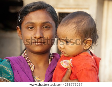 BEED, MAHARASHTRA, INDIA - March 23, 2012: girl with baby closeup in rural village Salunkwadi
