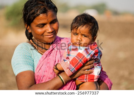 BEED, MAHARASHTRA, INDIA - March 25, 2012: lady Shepherd with her kid rural village Salunkwadi