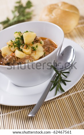 Beef and pork dish with bread roll - stock photo
