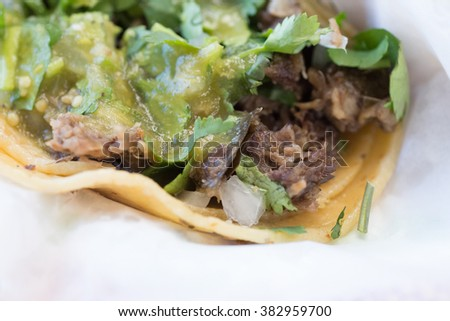 Beef and pork street tacos with garnishings, including onions, chives, salsa, and peppers - stock photo