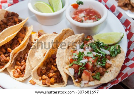 Beef and pork tacos with chopped tomato, onion and lemon